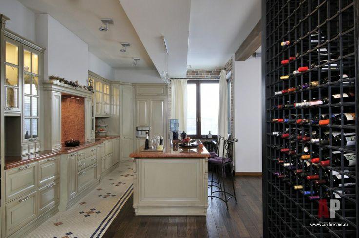 Дизайн интерьера двухэтажной квартиры в новостройке | На кухню Brummel Cucine, поставщик «Частный интерьер», можно попасть прямо от входной зоны, туда провожает винный шкаф, выполненный в «Мастерская Вениамина Скальника» по эскизу автора. Этот шкаф стал оригинальным исполнением несущей конструкции, которую обшили дубом и встроили внутрь кованые отделения для бутылок вина. Винный шкаф, таким образом, гармонично перекликается с кованой лестницей