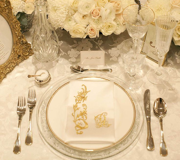 Voluptuous flower arrangements in white and champagne hues monogrammed silk napkins, imperial glassware and italian linens create a unique table setting for a memorable wedding -By Mitheo Events