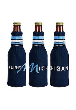 Add Pure Michigan style to almost any beverage bottle. Available in navy.   Specifications:   Knitted acrylic insulator fits most beverage containers from beer bottles to 2-liters   Woven Pure Michigan logo wrapped around bottle   Made in USA