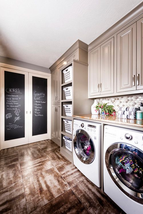 Laundry room, tan cabinets, rustic flooring, chalk board double doors, laundry basket cubbies | Nathan Taylor for Obelisk Home