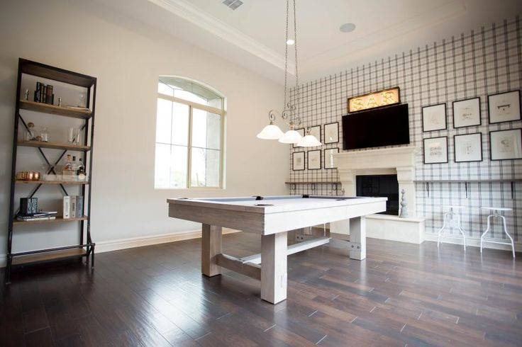This single-family transitional home features open spaces, high ceilings, and dark hardwood flooring. The kitchen includes a wide island and a subway tile backsplash. The dining room blends contemporary and traditional elements and has a metallic wallpaper with a midcentury modern flavor. The home's game room includes an accent wall papered in a white plaid pattern.