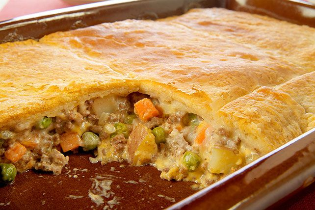 Ground beef and vegetables in a cheesy sauce are baked in a casserole topped with refrigerated crescent roll dough in this easy, weeknight-quick pot pie.