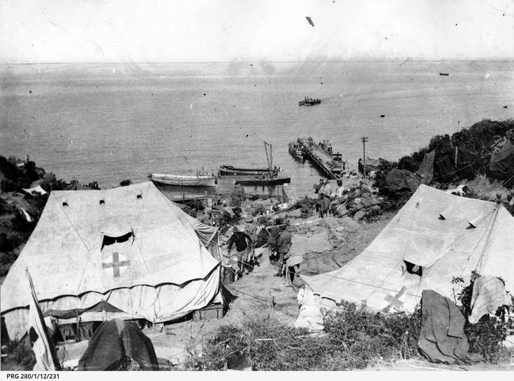 Medical tents near the landing jetty used by the 4th Australian Field Hospital at Anzac Cove, Gallipoli, Turkey; soldiers and landing craft appear in the background