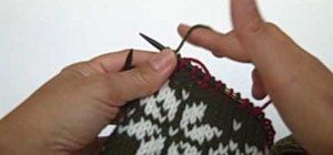 In this video, we learn how to knit with two colors of yarn. Carry your yarn in the hand that you are most comfortable with. Then, don't tension it around your pinkie so you can control the yarn. Put your dominant color over your forefinger and the accent finger on the bottom of your forefinger. This way, you will be able to turn your hands to decide which color is going to go up and over the needle. This just takes some easy practice to get used to.