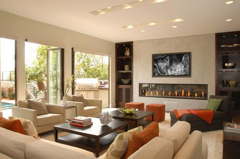 living rooms - modern fireplace ivory modern couches sofas chairs wood square coffee tables orange square ottomans orange silk pillows cushions gray modern chaise lounge green throw pillow beige walls bi-fold doors living room TV over fireplace