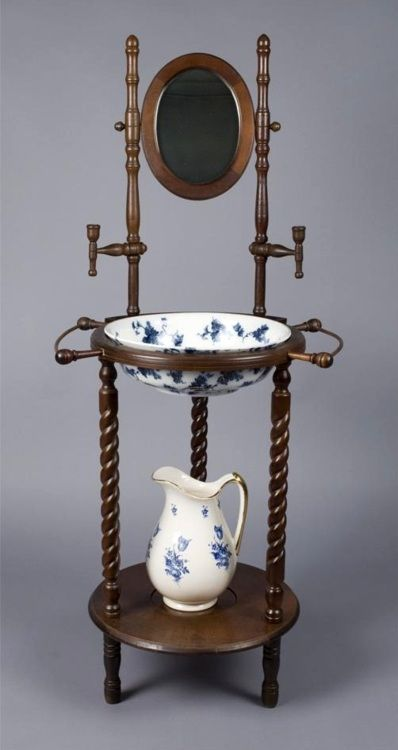 Fine Victorian Wash Stand, Pitcher & Basin: Finely carved with 3 barley twist legs, small oval mirror with 2 candle holders midway. Includes blue floral & gilt ceramic pitcher, & a flow blue & gilt highlighted Ridgeway basin / Live Auctioneers @ https://www.liveauctioneers.com/item/7758284_fine-victorian-wash-stand-pitcher-and-basin