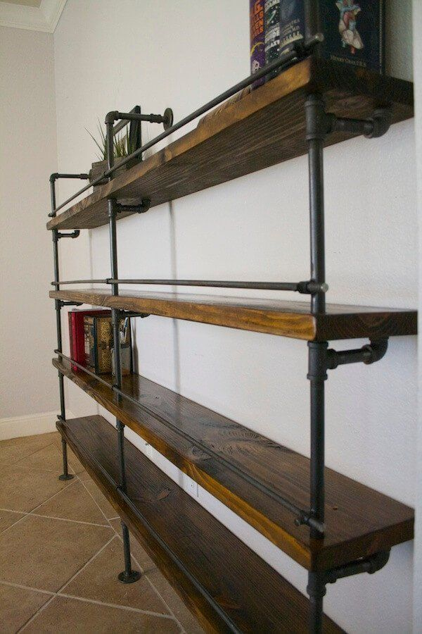 This industrial pipe shelving includes a bottle stop bar. This is great for library shelving or to hold alcohol. This shelving concept was originally purchased by Marriott Hotels for their shipping co