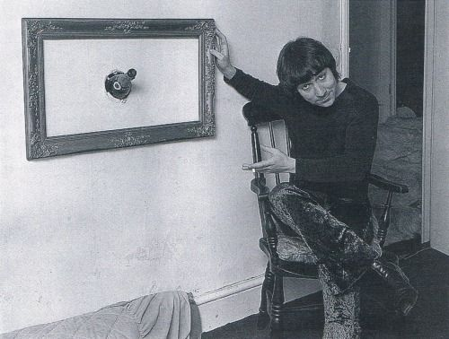 Keith Moon of The Who poses with a framed champagne bottle embedded