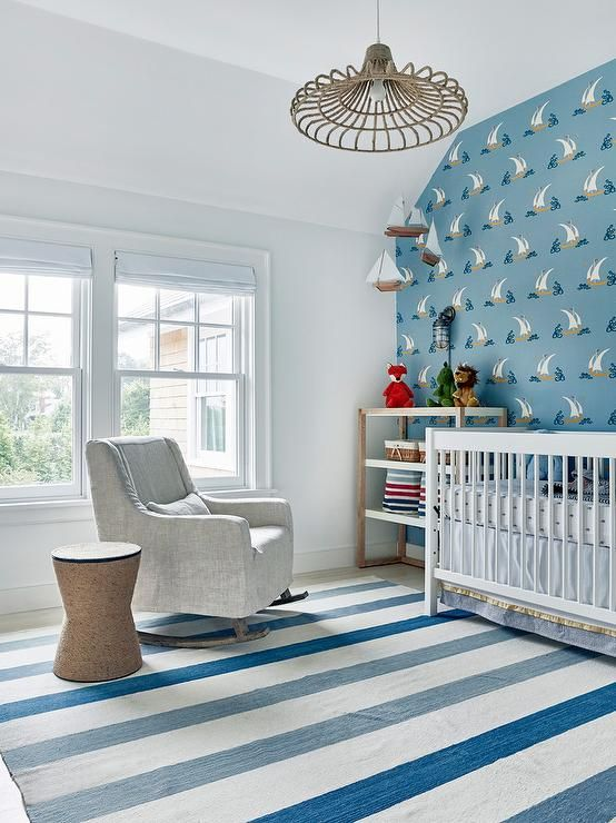 Blue And White Themed Boyu0027s Nursery Boasts A White Crib Placed Beside A Two  Toned Changing Table Positioned Beneath A Sailboat Mobile Hung In Front Of  A ...