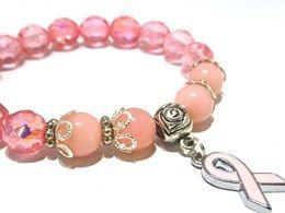 De armband is gemaakt op elastiek met daarop geregen roze glaskralen en facetkralen, gecombineerd met metalen kralenkapjes afgewerkt met een pink ribbon bedel.