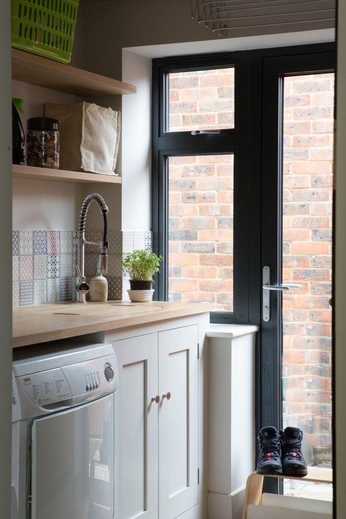 Sustainable Kitchens - Light and Airy Shaker Kitchen in London. Utility room with oak cabinetry painted in Farrow & Ball Pavilion Grey. Oak shelves hold laundry items. There is a slot for a washing and drying machine.