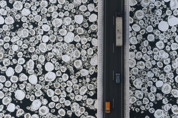 Kacper Kowalski new book Side Effects:  A lorry and cars travel on a road past the ice covered Vistula River near the village of Kiezmark du...