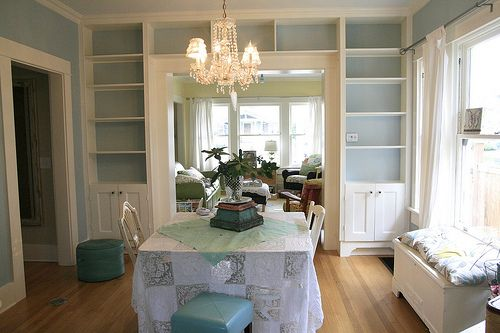 Inbuilt bookcase around room divider archway. Matching top of bookcase with coving and painting the same colour makes it look well integrated.