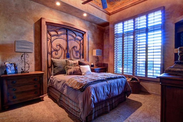 Mediterranean Master Bedroom with Set of Two Iron Scroll Table Lamps, Ceiling fan, High ceiling, Carpet