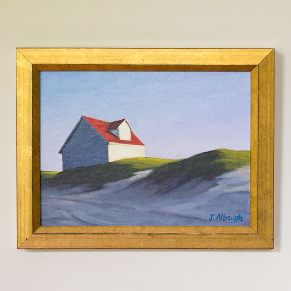 """Renowned local artist Joan Albaugh is recognized for her immaculate, windowless houses and barns. This sleek structure features a bold Nantucket red rood overlooking the dunes of Nantucket's beaches. Often compared to Edward Hopper, Albaugh's work is a true tour de force and """"In The Dunes"""" is no exception."""