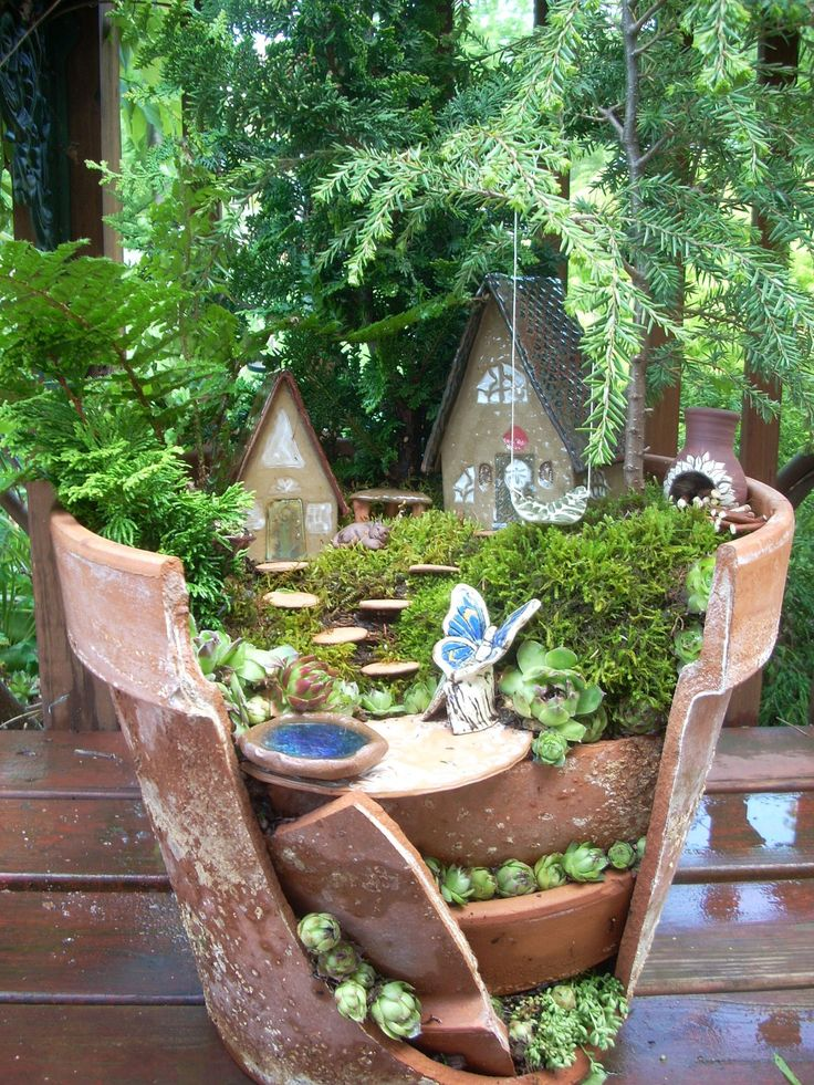 FAIRY GARDEN IN A BROKEN POT    This garden contains:  1-Large house  1-Small house  12 stepping stones  1 butterfly chair  1- chiminea  1- bench  1- wishing pond  1-swing with string  2- mini urn planters  1 sleeping cat  1- Patio rug  1- birdbath