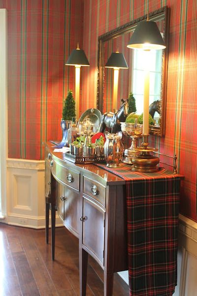 Handsome sideboard vignette - plaid walls and runner, silver, moss balls, brass candlestick lamps with black shades