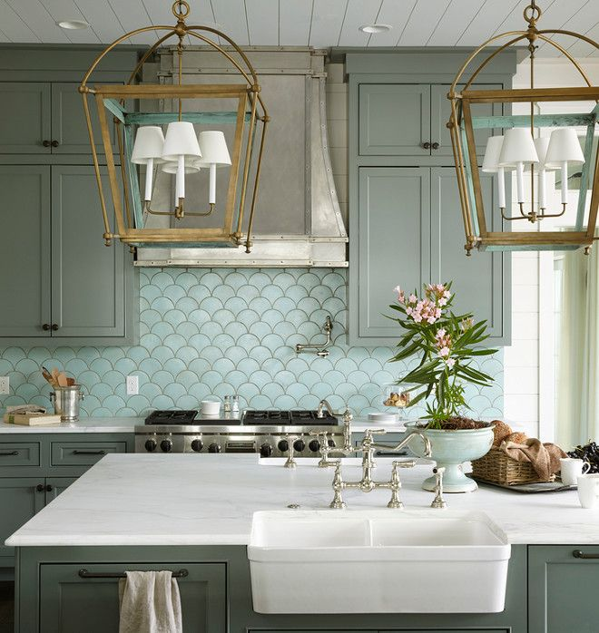 Kitchen: The brass lanterns above the island are Urban Electric Company Hamilton.  Lanterns: Urban Electric Company Hamilton –from $3,780 each.  Backsplash: The backsplash is Tabarka Studio Artisan Terracotta Fan Tile in Robin's Egg Blue installed upside down to create a fish scale effect.  Sink:  This island with white marble features twin Whitehouse Collection Fireclay Sinks facing each other.  Faucets: Perrin & Rowe.  Urban Grace Interiors.