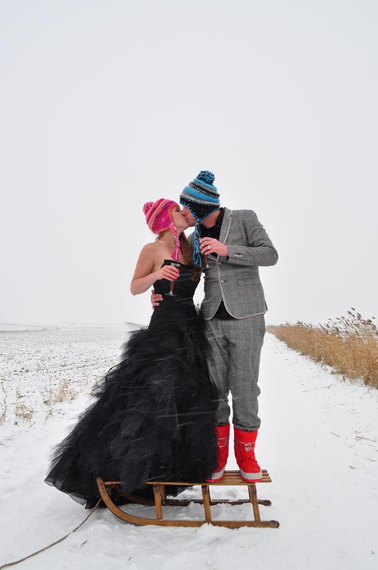 Stoer joh! Zwarte trouwjurk in de sneeuw, met muts. Zwart met rode corsage van vilt en jouw winterfeest kan beginnen.