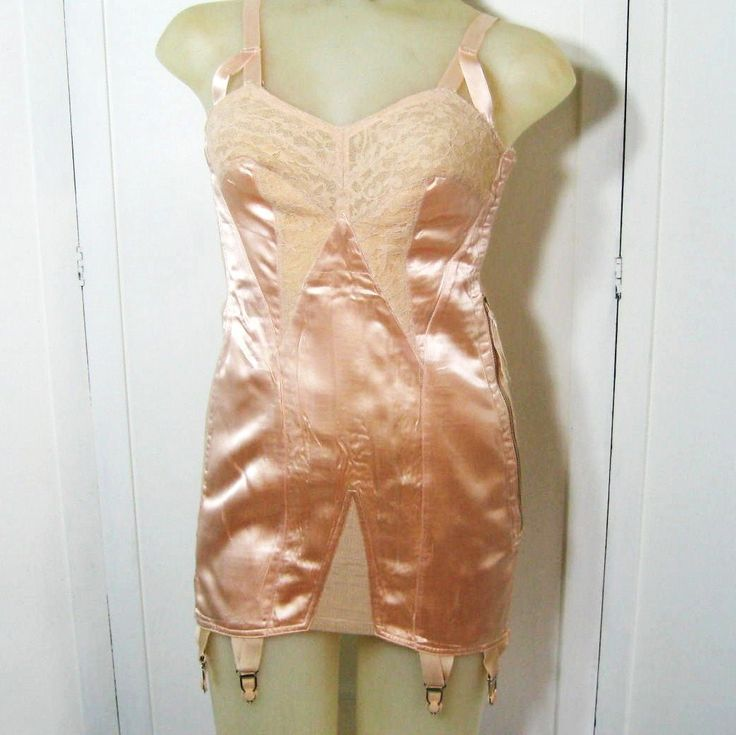Womens, late 1930s to early 1940s vintage, one piece, all in one foundation garment with six elastic and metal clip stocking garters.    Style..... Open bottom corselette, a combination step-in bra and girdle corset with side metal zipper/hook eye opening.    Color/Fabric..... Shiny peach rayon satin, lace, elastic, metal.    Era.....WWII    Label/Tag.......Sewn in cloth tag reads Rengo Junior Trademark reverse side reads Made with Darleen Super Elastic Yarns    Details.....Bra...
