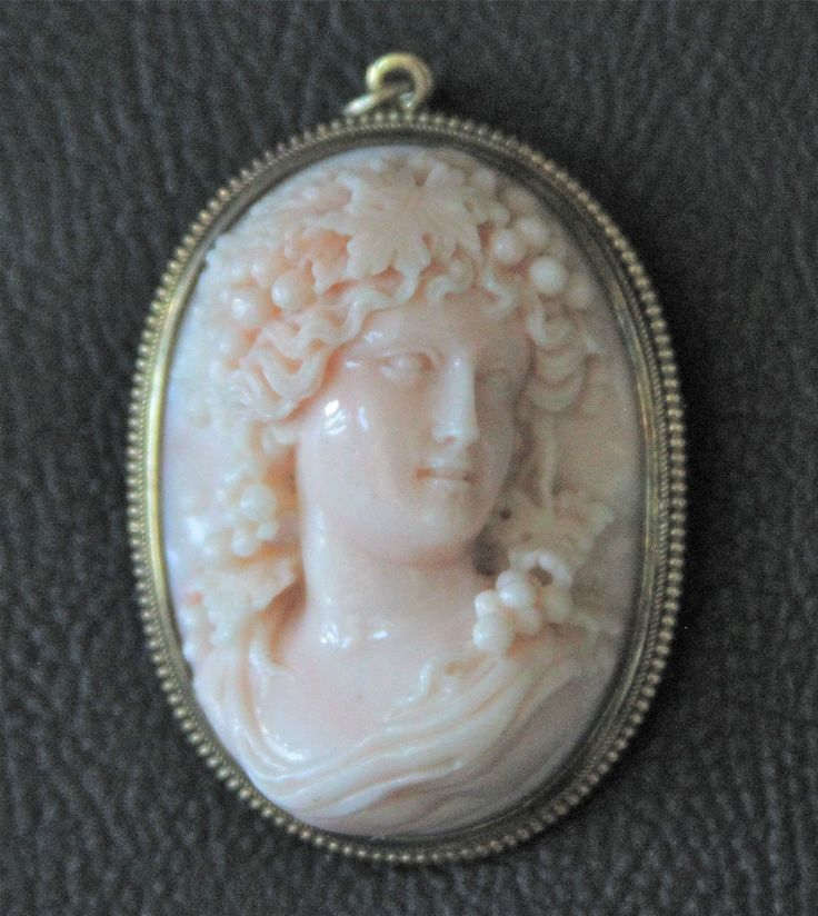 """Italian Coral High Relief Cameo in 18K Frame, Mid 19th Century $2 750 Very finely carved high relief Italian coral cameo brooch in 18K gold frame, circa mid-19th century. The cameo 1 7/8"""" X 1 5/8"""" X 5/8"""" thick and weighs 37.9 g total. Could be worn as brooch or pendant. Metal is unmarked, but tests 18K"""