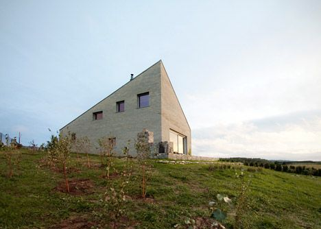 London-based designers Bartek Arendt and Kasia Bedra have built a barn-inspired house in Poland with a sloping triangular roof