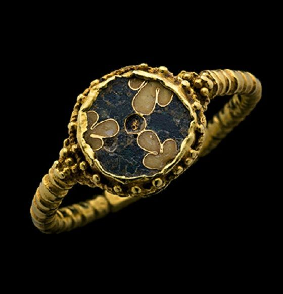 Medieval German Gold ring, the beaded hoop terminating at globules at the shoulders, supporting the round flat bezel with beaded border enclosing a cloisonné pattern of three trefoils on a dark blue ground. German, 9-11th centuries A.D.