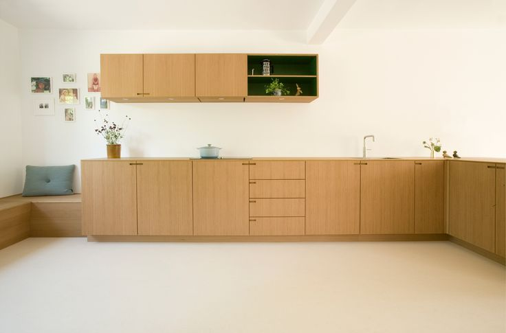 The kitchen is made of solid oak, with high pressure laminate in racing green on the insides, visible in the niches of the high cabinet, in the hanging cabinet, and in the built-in magazine rack.