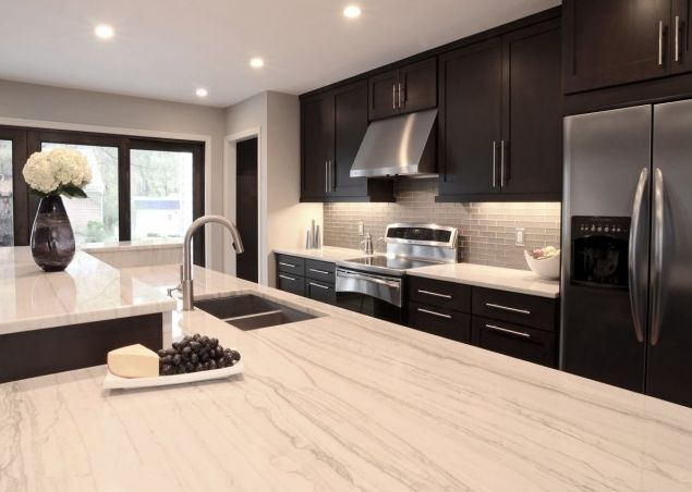 Amazing contemporary kitchen design with espresso stained kitchen cabinets & kitchen island, white stone counter tops, gray glass tiles backsplash and brushed nickel faucet.