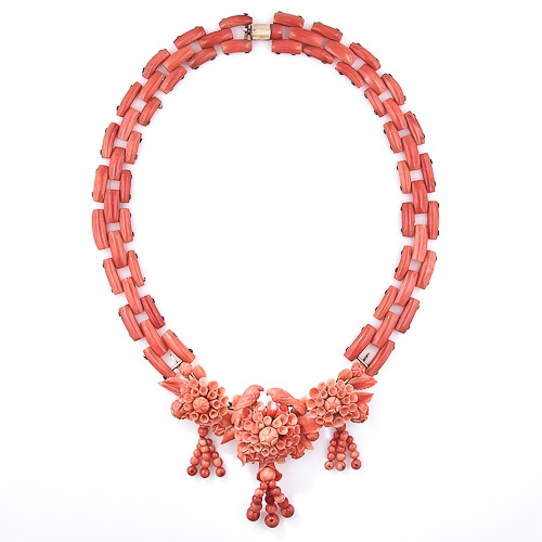 From mid-nineteenth century Italy comes this extraordinary carved coral necklace. The centerpiece is comprised of three flower blossoms, each of which is composed of individually hand carved petals and leaves, only three of which are missing. The three blossoms support fanciful beaded tassels dancing below and the central flower is crowned by a pair of finely carved love birds. The necklace portion is crafted in two parts and is composed of  geometric links to create a natural curve.