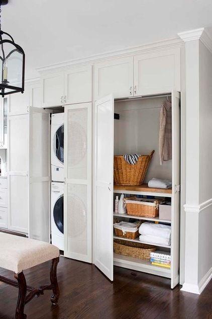 Laundry area in kitchen concealed behind white  cabinetry to match the kitchen cabinetry. transitional kitchen by TerraCotta Properties
