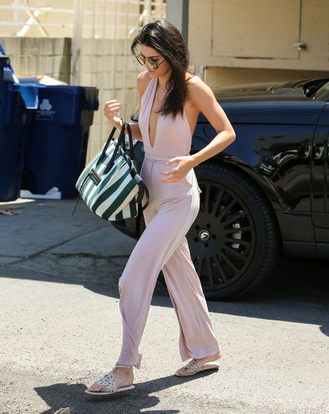 An actress she is not (yet?), but Jenner was movie star-level glam in Hollywood sporting a plunging, petal pink halter jumpsuit, mirrored aviator shades, pendant necklaces, geometric sandals, and a striped tote.