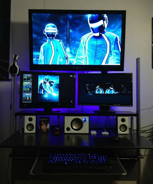 Mega monitor stacked up on a compact desk with purple neon for Man cave desk
