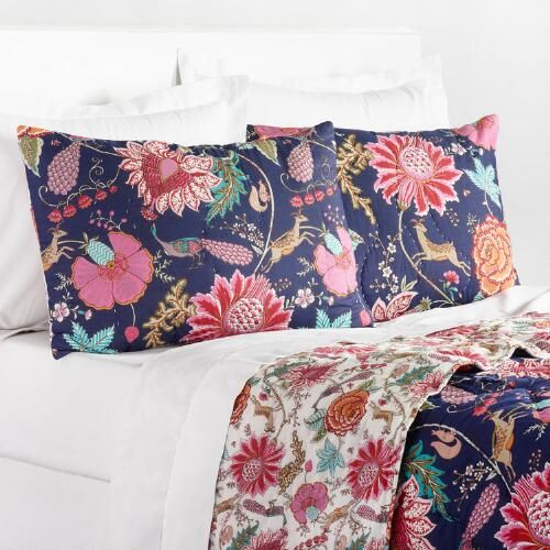 Hand-quilted and screen-printed by artisans in India, our exclusive cotton quilt features a striking pink and orange floral pattern on a deep indigo background. With a smaller scale design on a white background on the reverse, you get two looks with this plush quilt. Pair this quilt with its coordinating pillow shams to add some panache to your boudoir.