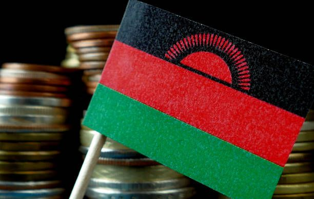 malawi flag waving with stack of money coins macro