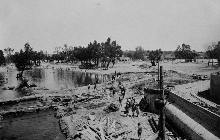 """Un ambicioso proyecto de divertimento acuático, embalsando el agua procedente del río Manzanares, cristalizaría con la construcción de lo que posteriormente se denominó """"Playa de Madrid"""", cuyas obras se pueden apreciar en esta fotografía. Estas instalaciones, finalizadas en 1932, sufrieron"""