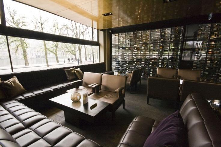 """""""Alleen de Taste Winebar was nog open. Kasper duwt de glazen deur open. De wijnflessen liggen er op transparante planken die alle muren vullen."""""""
