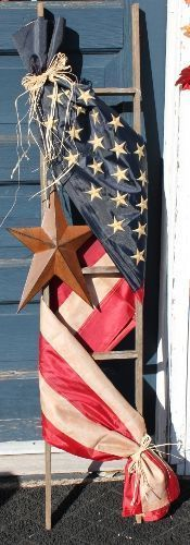 Adorned with a tea-stained Americana flag** and accented with a rusty star and raffia bow, this ladder will be a great addition to any Americana home decor or any front porch. This American Flag ladde