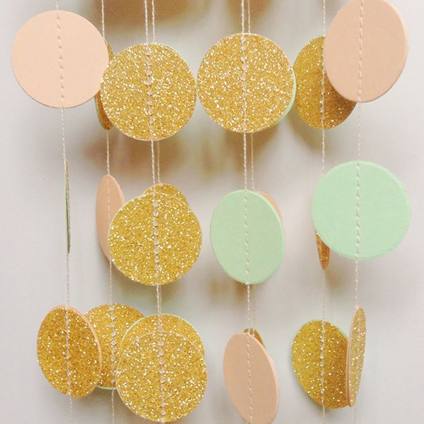Shimmering gold, mint, and peach paper garlands can serve as a pretty backdrop or table decoration.