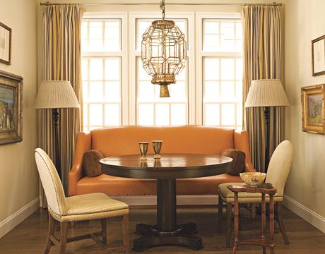 In a California beach house, designer Chad Eisner used an orange and beige palette to create a cozy bungalow feeling. The dining area has a banquette covered in top-stitched custom-dyed leather from Caldelle, Ltd. Chair upholstery and the unlined striped curtain fabric are from Clarence House. An agate bowl on a 1940s Jansen side table is from Ruzzetti and Gow and the vintage Moroccan lantern was found at Kim Fiscus. Center table and lamps were designed by Chad Eisner.