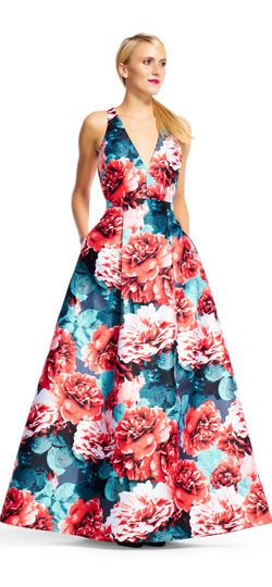 Adrianna Papell | Floral Print Mikado Dress with Ball Skirt | Be the main event at every gala when waltzing in dressed in this bold floral ball gown. Simple yet stand out, this formal dress features a halter silhouette, v-neckline, and a floral print that pops off the mikado fabric. The full ball skirt with pockets cannot be missed when checking out this style. Team this evening gown up with a neutral heel and small sparkling accessories.