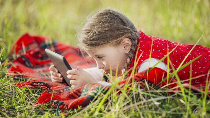 Tyttö makaa nurmikolla tablettitietokoneen kanssa.