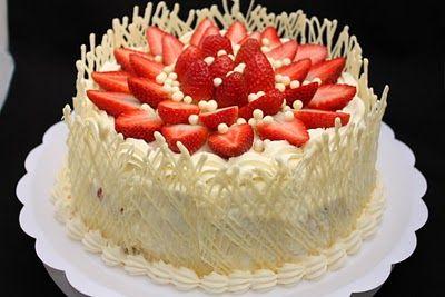 Este bolo foi feito com massa branca, recheio de brigadeiro branco e ganache branco com morangos.