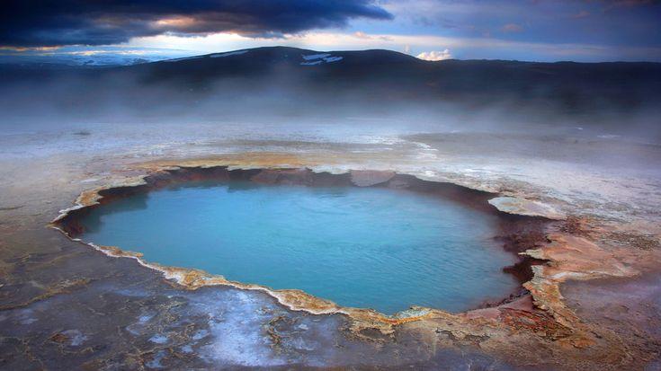 """Ebene der heißen Quellen - magisch, aber kaum real.""""Hveravellir"""" bedeutet auf Isländisch so viel wie """"Ebene der heißen Quellen"""". Hier, im Westen Islands, zeigen sich viele typische Merkmale von Hochtemperaturgebieten. Aus den Tiefen des Erdinneren treten Heißwasserquellen an die Erdoberfläche, wie etwa das von Sinterterrassen umgebene """"Blahver"""" (""""Blaue Quelle""""). Die vulkanische Landschaft wirkt wie aus einer anderen Welt: irgendwie magisch, aber kaum real."""