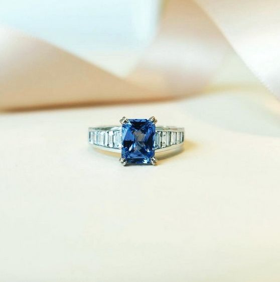 Naveya & Sloane bespoke octagonal blue sapphire centre stone, set in a split claw basket. Crafted in platinum, with trapezoid cut diamonds channel set into the band.