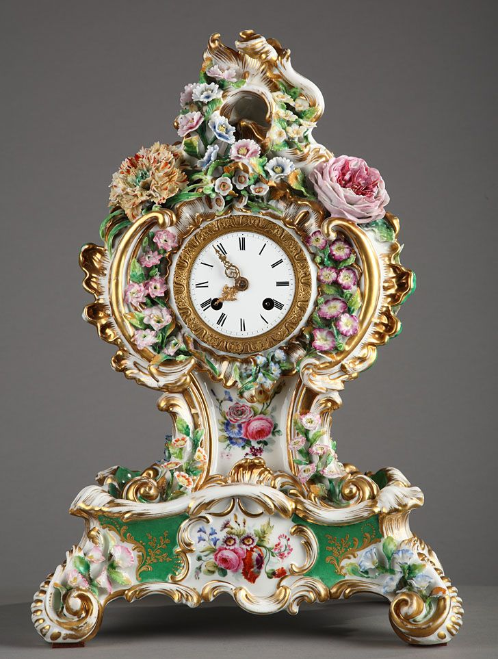 Fine porcelain, violin-shaped mantle clock signed Jacob Petit, richly decorated with polychrome flowers accented with golden winding sheets and scrolls on white and light green background. H
