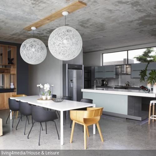 Ein modernes Einbauregal aus Holz dient hier als dekorativer Raumtrenner zur Küche. Die Betondecke und ausgewählte Designermöbel verleihen dem Raum einen  …