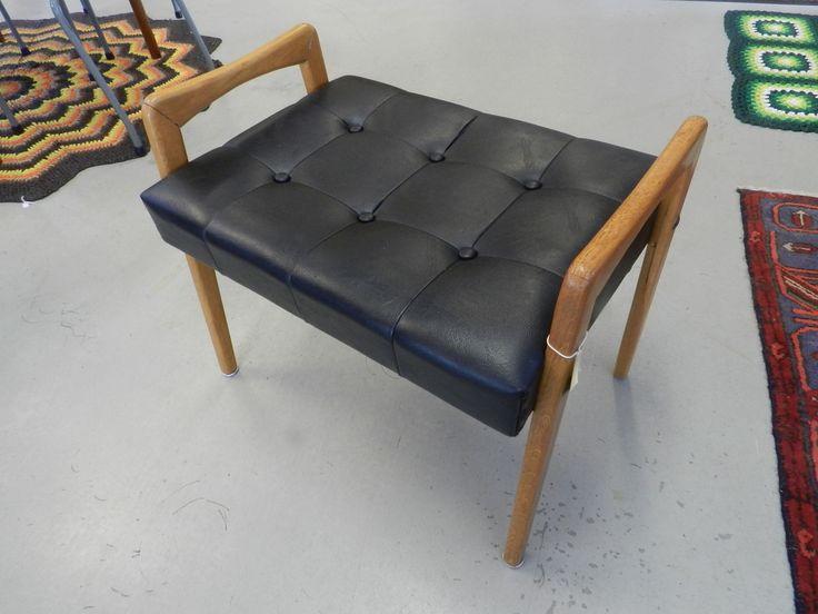 Pall med knappstoppad sits i svart skinn. 58x41x49cm