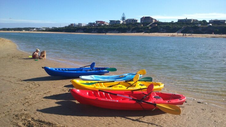 Lazy summer days at the beach. Canoes and kids playing in the sand.