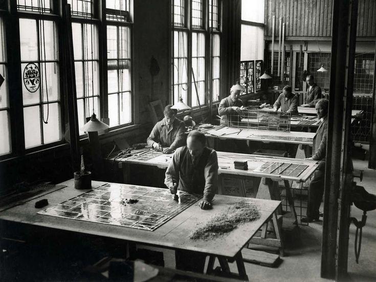 Glas-in-lood. Mannen zijn in een hal van het bedrijf  Rein Hack bezig glas in lood te zetten. Ze werken aan grote tafels en gebruiken verschillende gereedschappen. Den Haag, Nederland, 1924.